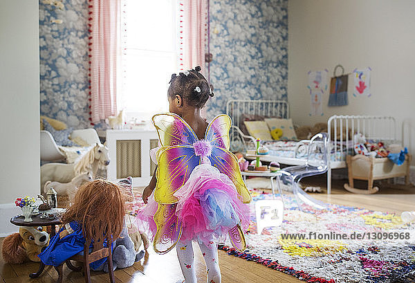 Rear view of girl dressed in fairy costume walking in bedroom