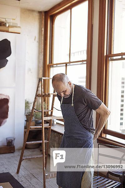 Artist wearing apron by window in workshop
