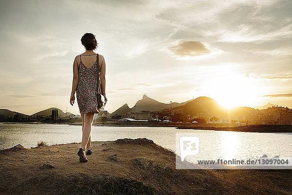 Rückansicht einer Frau  die auf einem Weg am Fluss gegen den Himmel geht