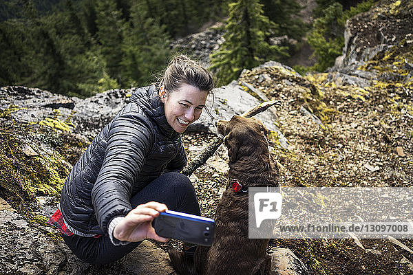 High angle view of woman clicking selfie with dog on mountain cliff