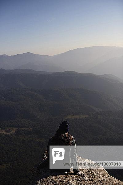 Hochwinkelaufnahme einer Frau  die auf einer Klippe vor Bergen sitzt
