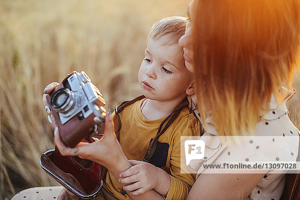 Mother teaching son to photograph with vintage camera on field