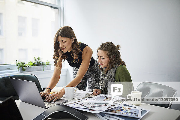 Female colleagues using laptop computer while working at conference table with printouts in board room
