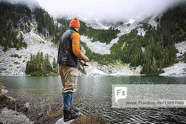 Rückansicht eines Mannes  der am See gegen Berge fischt