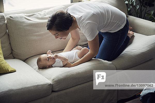 Schrägansicht einer glücklichen Mutter  die ihren Sohn zu Hause auf dem Sofa liegen sieht