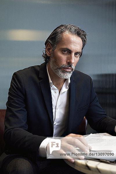 Porträt eines selbstbewussten Geschäftsmannes  der ein Smartphone benutzt  während er im Büro sitzt