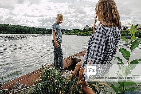 Brother looking at sister walking into rowboat