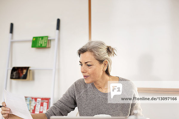Concentrated woman holding paper while working at home