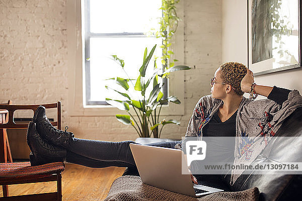 Thoughtful woman looking away while using laptop on sofa at home