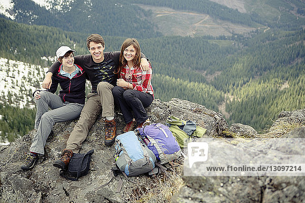 Portrait of happy friends sitting on top of mountain