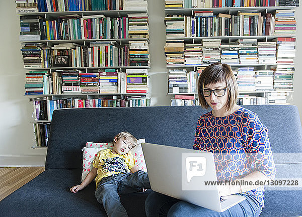 Mother using laptop computer while sitting with son on sofa at home