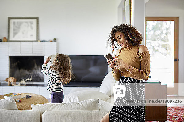 Mother using mobile phone while daughter playing with toys at home