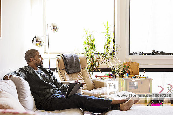 Man with tablet computer looking away while sitting on sofa at home