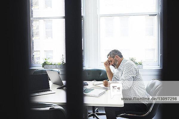 Seitenansicht eines Geschäftsmannes mit dem Kopf in Handschrift am Konferenztisch durch ein Fenster im Büro gesehen