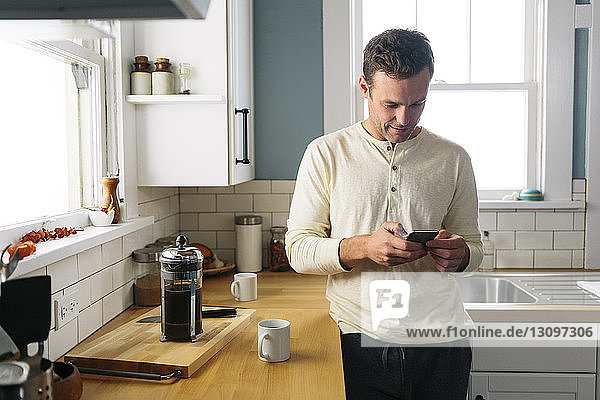 Man using smart phone while leaning by kitchen counter at home