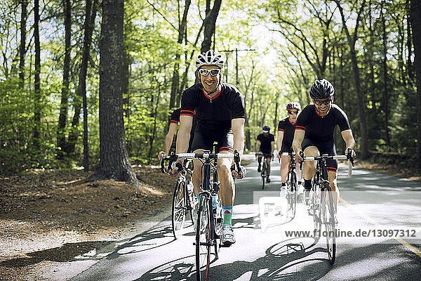 Smiling male cyclist riding bicycle with friends on country road