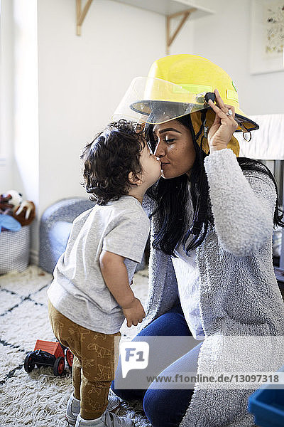 Son kissing mother wearing firefighter's helmet at home