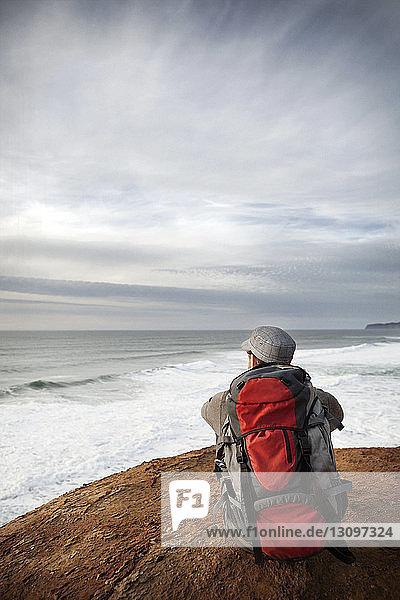 Mann sitzt am Rand einer Klippe