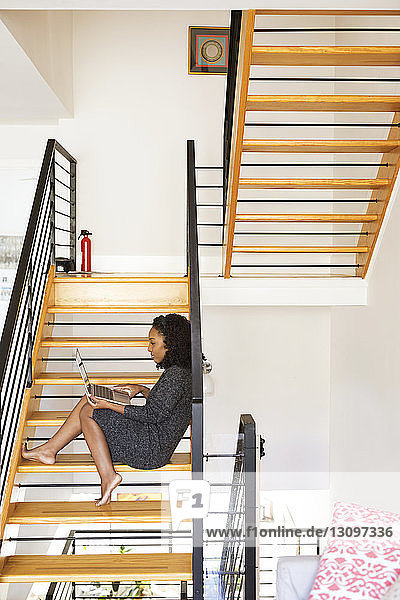 Seitenansicht einer Frau  die einen Laptop-Computer benutzt  während sie zu Hause auf einer Treppe sitzt
