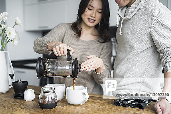 Woman with boyfriend pouring coffee in cups at table