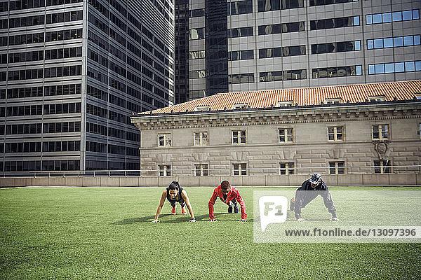 Athleten machen Liegestütze auf Grasfeld mit Gebäuden im Hintergrund
