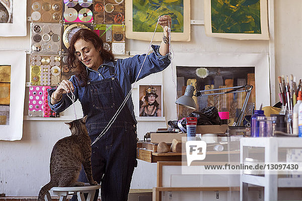 Happy female artist playing with cat in workshop