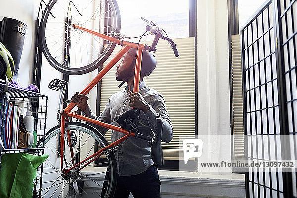 Geschäftsmann entfernt Fahrrad vom Gepäckträger im Kreativbüro