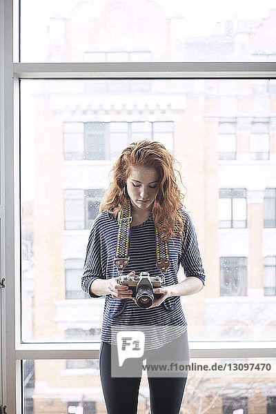 Woman photographing while standing by window at home