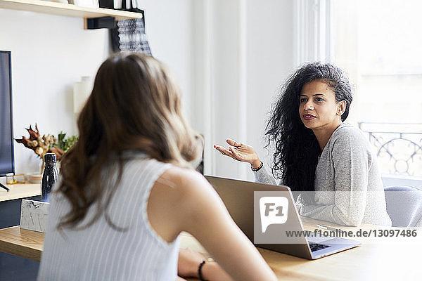 Geschäftsfrau gestikuliert im Gespräch mit einer Kollegin am Schreibtisch im Büro