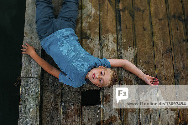 Overhead view of boy lying on wooden pier