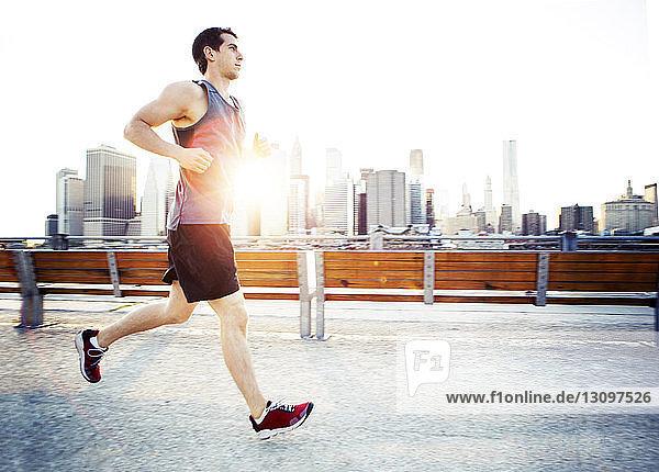 Seitenansicht eines Mannes  der auf einer Bank gegen das Stadtbild rennt