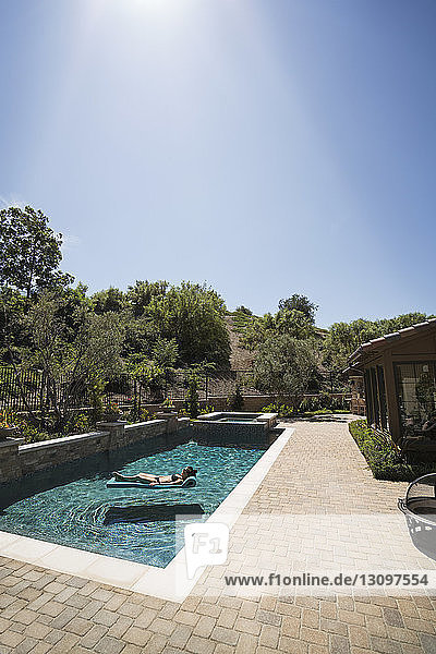 Woman relaxing on pool raft at swimming pool