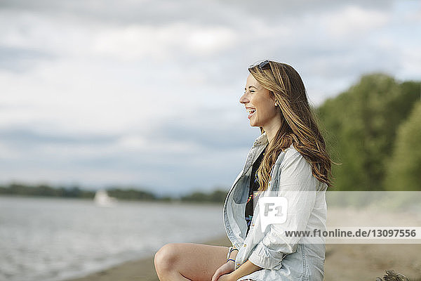 Side view of happy woman sitting at riverbank