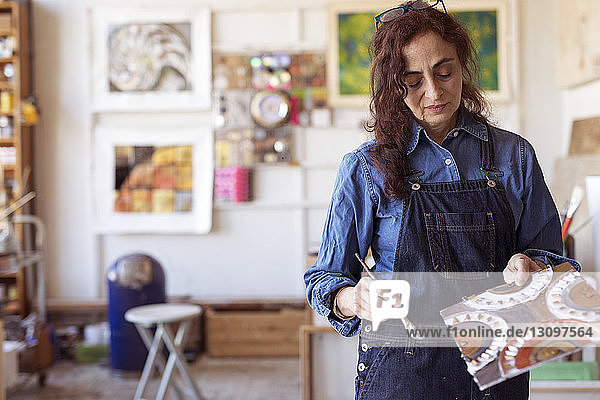 Female artist holding artwork with paintbrush in workshop