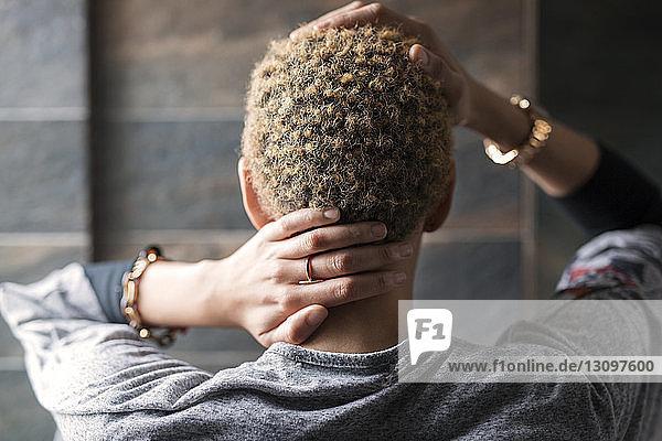 Rückansicht einer Frau,  die zu Hause Nacken und Haare berührt