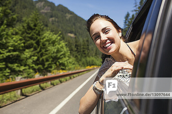 Portrait of happy woman looking through window while traveling in car