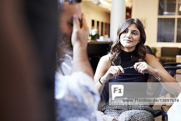 Selbstbewusste junge Geschäftsfrau betrachtet männlichen Kollegen,  während sie im Büro sitzt