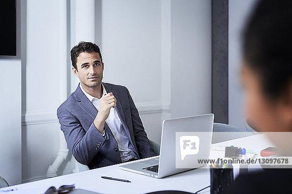 Geschäftsmann hört Kollegen am Konferenztisch bei Bürobesprechung zu