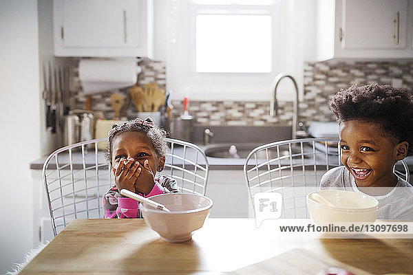 Cheerful brother and sister looking away while having breakfast in kitchen