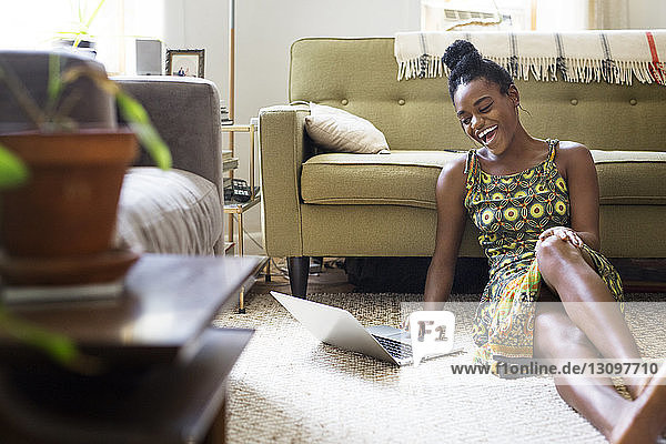 Happy woman using laptop computer at home
