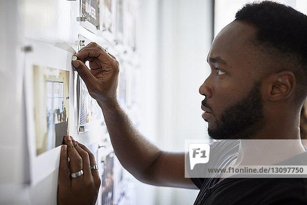 Seriöser Geschäftsmann hängt Fotoausdrucke am Schwarzen Brett im Büro an