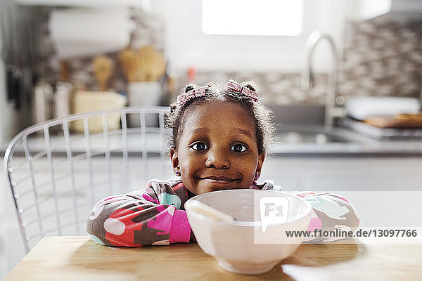 Portrait of cute girl leaning on table with breakfast bowl in foreground