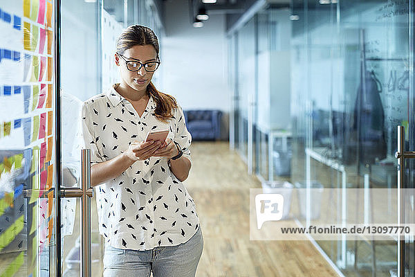 Businesswoman using mobile phone while leaning on glass door at corridor