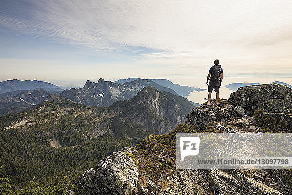 Rear view of carefree hiker with backpack standing on mountain against sky