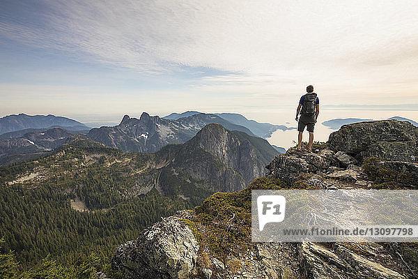 Rückansicht eines unbekümmerten Wanderers mit Rucksack  der auf einem Berg gegen den Himmel steht