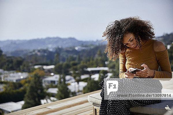 Frau benutzt Mobiltelefon  während sie auf Liegestuhl gegen den Himmel sitzt