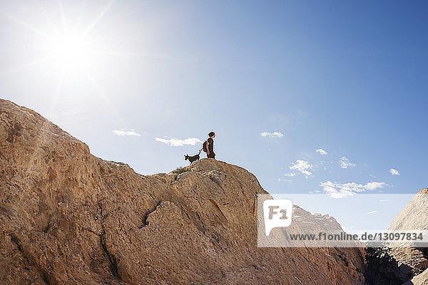 Tiefwinkelaufnahme eines Mannes mit Hund  der auf einem Berg vor blauem Himmel steht