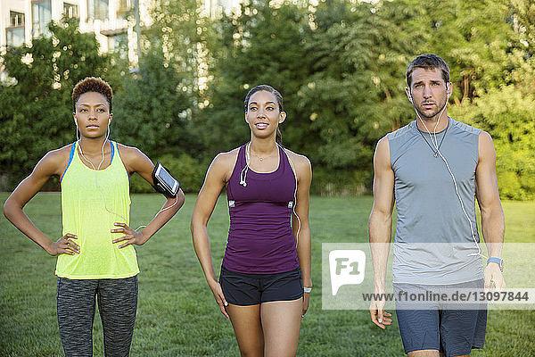 Zuversichtliche Athleten gehen auf dem Rasenfeld des Parks