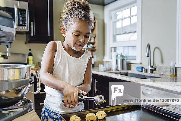 Girl preparing chocolate chip cookies in kitchen