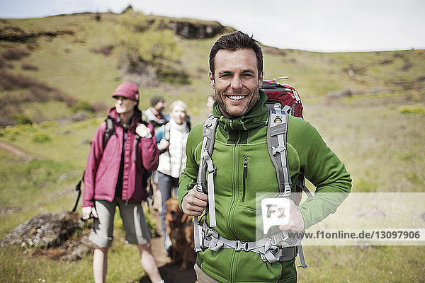 Portrait of happy male hiker standing with friends on hill
